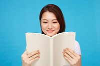Young woman reading book, smiling