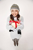 Young woman wearing knit hat and holding gift box, portrait