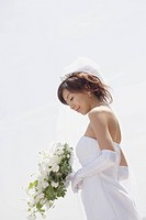 Bride holding bouquet, low angle view