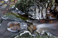 Ice formed on rocks in mountain stream, with water rushing past, Cumbria, England, winter