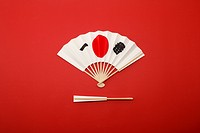 Two Japanese folding fans on red background, close_up