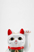Beckoning cat on white background, close_up