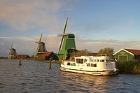 A boat and windmills in the light of the setting sun, Open_air museum Zaanseschans at the river Zaan, Netherlands, Europe