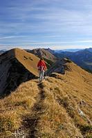 Woman hiking on trail at Fleischbank, Karwendel range, Tyrol, Austria