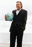 A man holding a ball shaped as a globe.