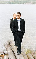 Two smiling businessmen in suits walking on driftwood