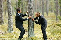 Two businessmen in suits playing in forest