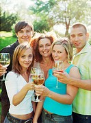 Portrait of group of friends toasting with wine in garden