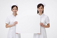 Two female nurses holding blank placard, smiling, portrait
