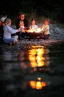 Children and man grilling at Lake Starnberg, Bavaria, Germany