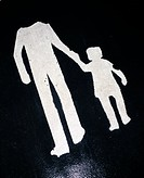 Close up of white shapes of man with child on asphalt road
