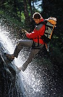 Man climbing, descending down a waterfall. Lake Sylvenstein, Upper Bavaria, Bavaria, Germany