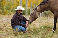 A cowboy kneels down to have a moment with his horse in Northern Alberta, Canada.