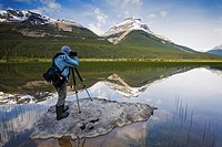 A Photographer sets up a morning landscape photo at Rampart Ponds in Banff National Park, Alberta, Canada