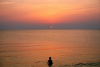 A child swimming in the ocean at sunset.