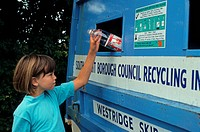 Recycling, child putting waste plastic bottle into recycling bin, England
