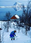 Elderly woman shoveling snow at home in Lofoten Islands, Norway