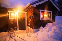 Country home in Dalarna, Sweden in winter with skiis, sled and snow shovels under porch light