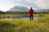 Middle age male hiker at Cascade pond overlooking Rundle Mountain, Banff National Park, Canada.