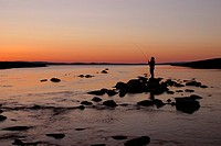A person fishing on a lake at dusk, Sweden