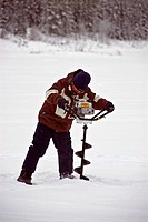 Fisherman using ice auger, boring hole in lake ice for ice fishing, Yukon Territory, Canada, winter