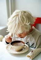 A boy drinking hot chocolate.