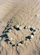 Stones forming a heart in the sand.