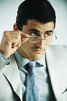 Businessman looking away, lowering glasses, portrait