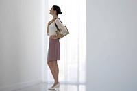 Woman standing beside window, looking up, side view