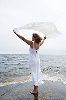 A woman holding a white scarf in the wind by the sea Sweden.