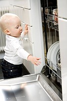 A baby standing by a dishwasher Sweden.