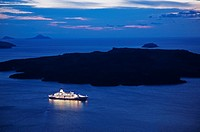 Illuminated Luxury cruise ship and Nea Kameni island across from Santorini at dusk, Greece