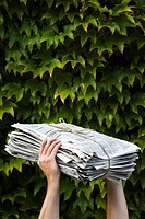 A man holding newspapers for recycling.