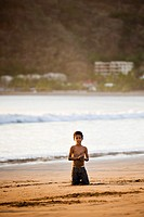 Little boy kneeling in the sand on the shore of San Juan del Sur, Nicaragua