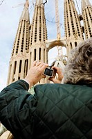 A woman taking photographs of the Sagrada Famlia in Barcelona Spain.