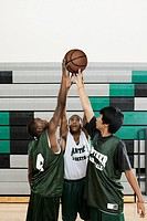 Basketball players reaching for ball in gym