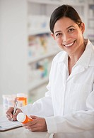 Hispanic pharmacist holding prescription bottle