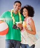 Couple on beach with tropical drinks