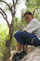 African boy sitting on rock in park