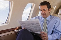 Hispanic businessman reading newspaper on airplane