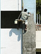 A Painter is seating on a cradle for building's exterior painting work