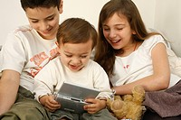 Brothers and sister playing to a video game Nintendo DS.