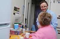 Independent nurse, in Vénissieux, France. Independent nurse at the home of a diabetic patient of type 1. The nurse talks with the patient.