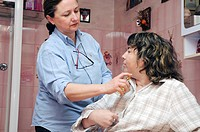 Independent nurse, in Vénissieux, France. Home of a hemiplegic patient. Patient care and help for dressing_up and washing.