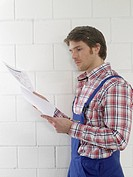 Man wearing work wear is holding construction plans