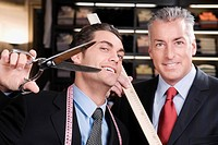 Tailor holding a scissors with a businessman in a clothing store