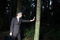 Businessman in forest holding briefcase
