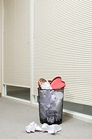 Office wastepaper basket full of paper and discarded valentines chocolate box