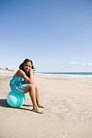 Girl sitting on a beach ball