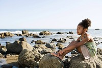 Girl sitting on rocks at the beach (thumbnail)
